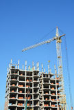 Tower Crane and Building Constructors on Construction Site. Building with two cranes on construction site with builders. Stock Photo