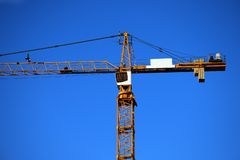 The tower crane with a cabin of the operator against the background of the blue sky. The rotary crane of boom type with the arrow fixed in the top part of stock images