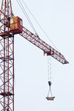 Tower crane carries load in bucket gas cylinders for cutting and welding. Royalty Free Stock Photos