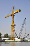 Tower crane at construction site near river Royalty Free Stock Photography