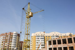 Tower crane on construction site on the background of new reside. Tower crane on construction site against the background of new buildings Royalty Free Stock Photo