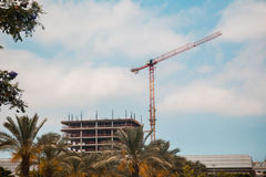 Tower crane in construction site over blue sky with clouds Royalty Free Stock Photos