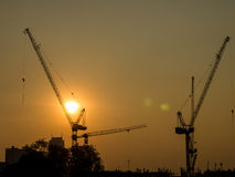 Tower crane on a construction site at sunrise. Taken from Bangkok, Thailand Royalty Free Stock Photos