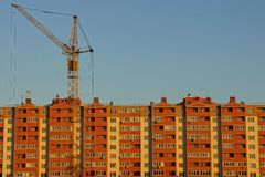 Tower crane in front of a block of houses against a blue sky Stock Images