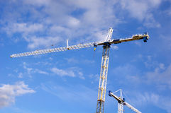 Tower crane hoisting load in a sunny day Stock Images