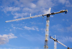 Tower crane hoisting load in a sunny day Royalty Free Stock Photo
