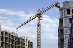Tower crane between houses. Royalty Free Stock Photos