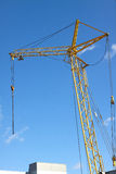 Tower crane on industrial building construction over blue sky Stock Image
