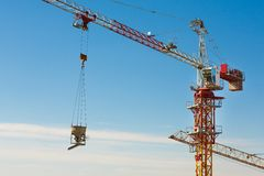 Tower crane lifting up a cement bucket at construction area Royalty Free Stock Photography