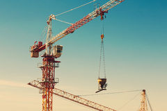 Tower crane lifting up a cement bucket at construction area Stock Images