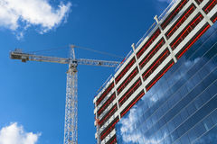Tower crane and modern building under construction Stock Photos