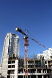 Tower crane over concrete frame of building construction Royalty Free Stock Image