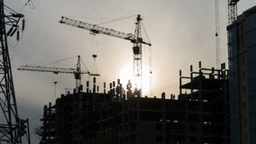 Tower crane work, in the evening on the construction site. Timelapse. Construction site with working crane at dusk stock footage