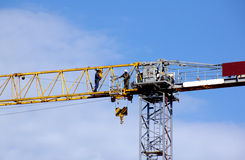 Tower Crane and Workers Against Blue  Sky Royalty Free Stock Photography