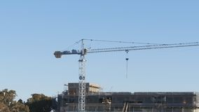 Tower crane works on building a house. Big Tower crane works on building a house stock video