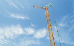 Tower crane. Yellow construction tower crane against blue sky Royalty Free Stock Image