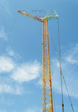 Tower crane. Yellow construction tower crane against blue sky Royalty Free Stock Photography