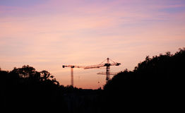 Tower cranes against the background of a bright sunset. Colorful sky over the city. Building on a beautiful bright background Royalty Free Stock Photos