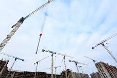 Tower cranes against the blue sky with the roofs of multi-storey buildings under construction from below royalty free stock photos