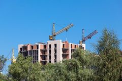Tower cranes and building construction. Construction a multi-storey building with tower cranes against the blue sky Stock Photography