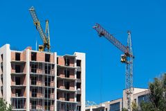 Tower cranes and building construction. Construction a multi-storey building with tower cranes against the blue sky Stock Image