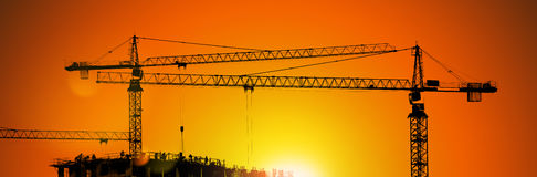 Tower cranes and building silhouette with workers at sunrise. Stock Photos