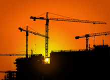 Tower cranes and building silhouette with workers at sunrise. Royalty Free Stock Photography