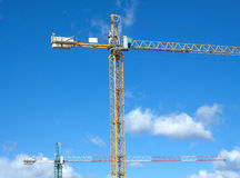 Tower cranes in construction process over blue sky with clouds Royalty Free Stock Images