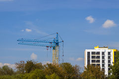 Tower cranes on a construction site near building and green tree Stock Photos