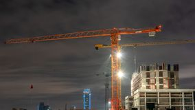 Tower cranes at a construction site in the night city stock image