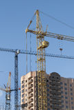 Tower cranes on the construction site. Three tower crane at a construction site next to the new building Royalty Free Stock Photography