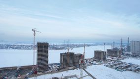 Tower cranes at the construction site. In winter time lapse, aerial view stock video