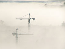 Tower Cranes through fog Stock Photo