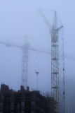 Tower cranes and fog Royalty Free Stock Photo