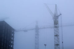 Tower cranes and fog Stock Photo