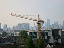 Tower Cranes in front of City Skyline. A tower crane with a city skyline behind it doing construction work stock image