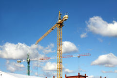 Tower cranes on industrial building construction over blue sky Stock Photo