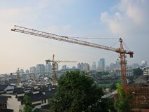 Tower Cranes Over City. Tower cranes (3 cranes) building new construction in China. The city skyline is in the background stock photos