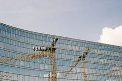 TOWER CRANES REFLECTED IN GLASS Stock Photo