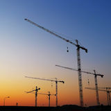 Tower Cranes Sunset. Construction site with silhouette of tower cranes on sunset, ready to start working Stock Image