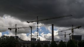 Tower cranes at work under thunderstorm in a district under construction in the suburbs of the city of Tallinn, Estonia stock photo