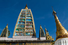 Tower depicting the life of Buddha, surrounded by spires at the Royalty Free Stock Images