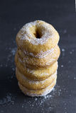 Tower of Doughnuts on a dark background. Five sugared ring doughnuts on a and dark background royalty free stock photo
