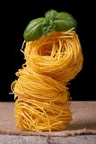 Tower of dry pasta nest closeup with green basil Stock Photos