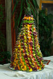 A tower of exotic fruits stands on a white table Stock Image