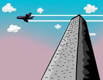 Tower Flyby. A passenger plane flies over a tall skyscraper Stock Image