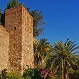 Fortified tower of the Alcazaba moorish castle, Malaga. Tower of the fortifications of the Alcazaba moorish castle, Malaga, surrounded by green plants on a sunny Stock Photography