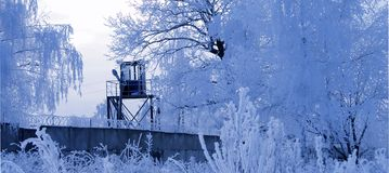 Tower And Frosty Trees. Patrol tower with razor wire fence and blue frosty trees Royalty Free Stock Image