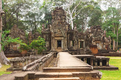 Tower and galleries in Angkor Thom, Siem Reap, Cambodia. Tower and galleries and walking tourists at sunny morning in Angkor Thom, Siem Reap, Cambodia Royalty Free Stock Photo