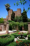 Tower and garden, Alcazaba de Malaga, Spain. Patio below the Puerta de los Cuartos de Granada, Alcazaba de Malaga, Malaga, Costa del Sol, Malaga Province Royalty Free Stock Photos